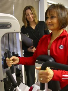 Female client working with a personal trainer on an exercise machine