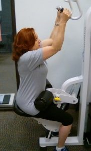 Female client strength training on a machine