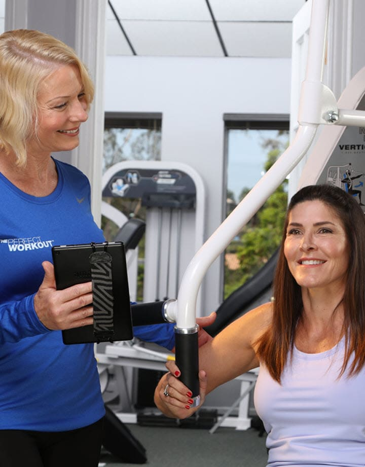 woman on chest press machine with female trainer