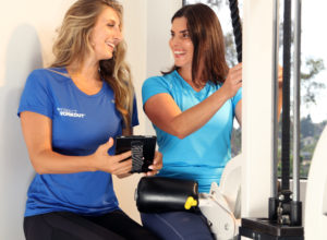 woman on workout machine with female trainer