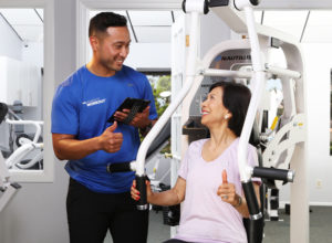 woman on chest press machine with male trainer