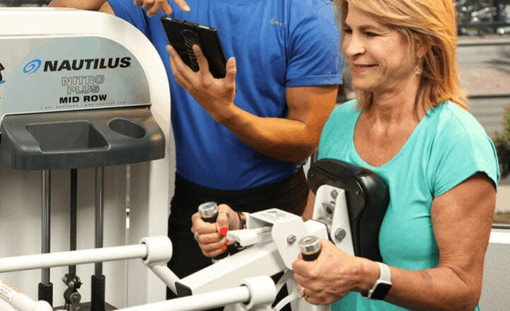 female client strength training on a nautilus machine with a personal trainer