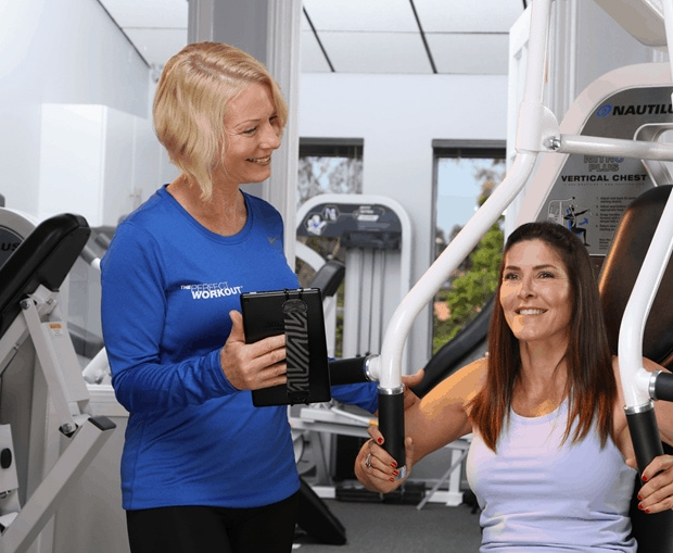 female client with a female personal trainer on a machine