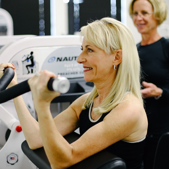Female Client working out safely in person