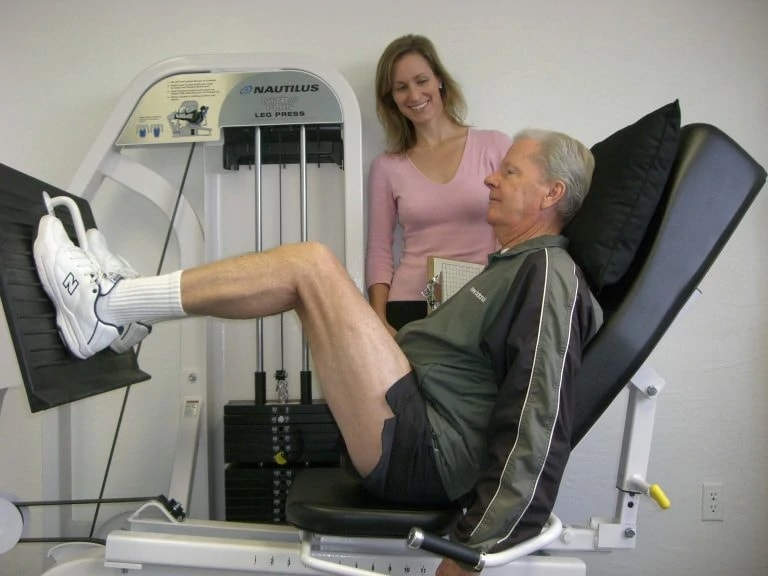 male client with female trainer doing a leg press on a machine