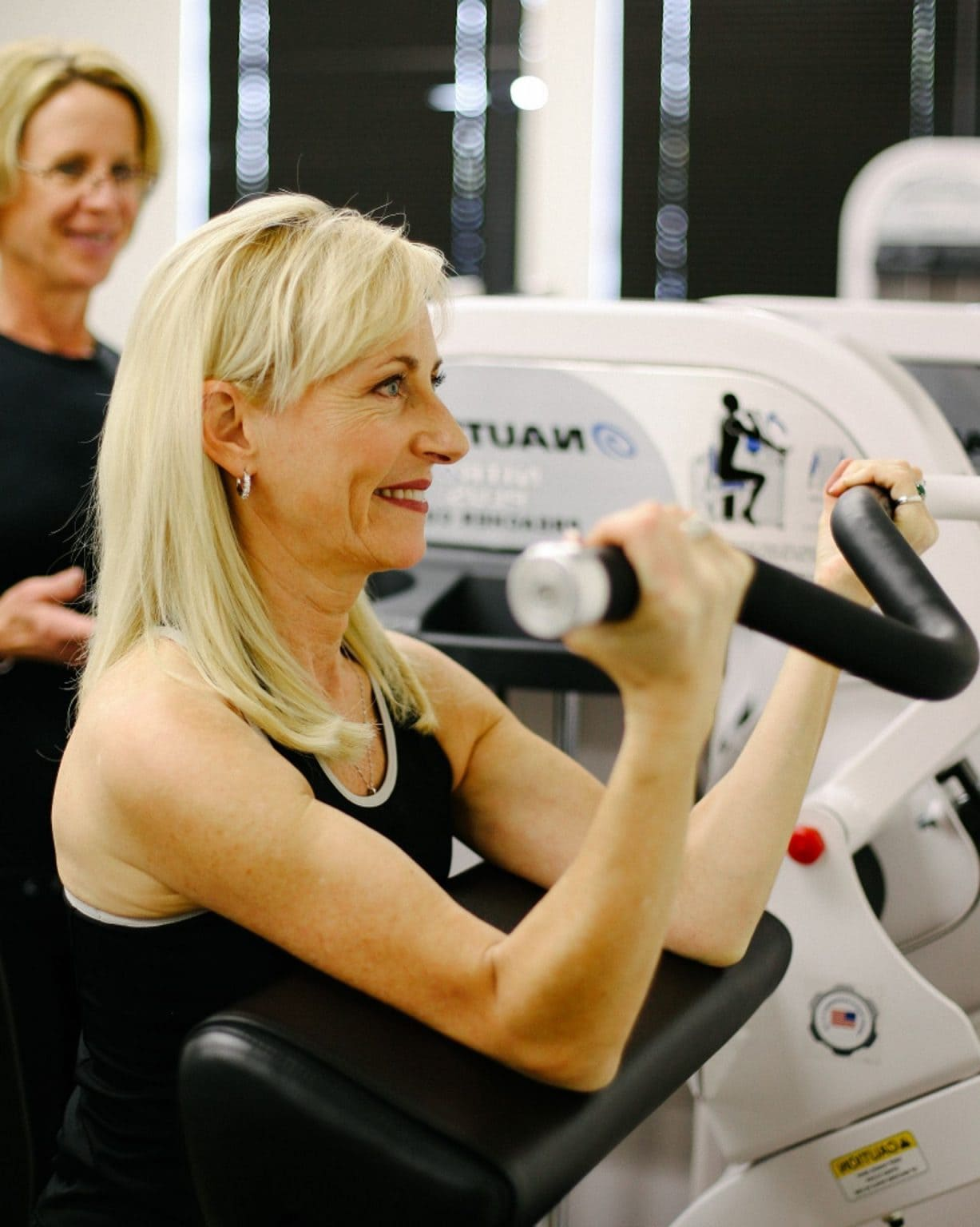 woman doing bicep curl with personal trainer
