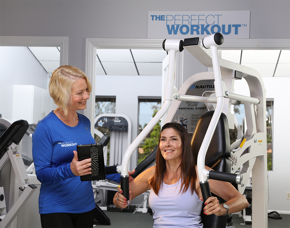 Trainer coaching female client on chest press