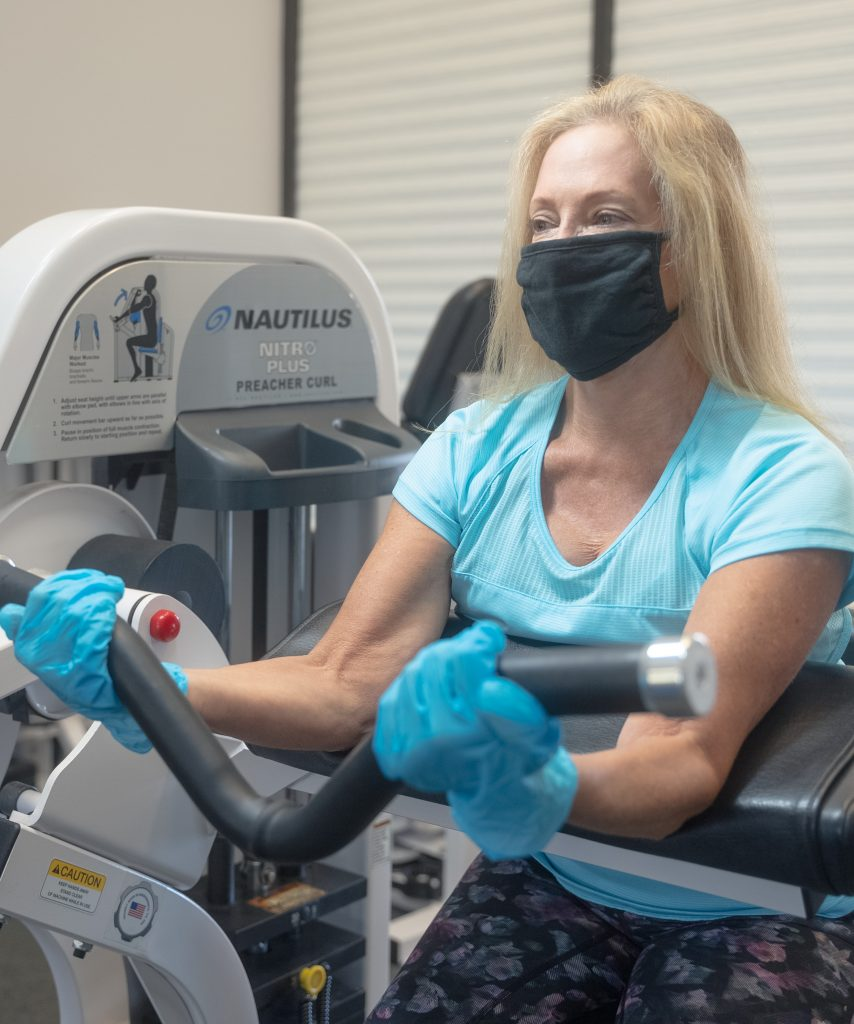 Client in mask in gloves safely working out in medical fitness facility during a personal training session