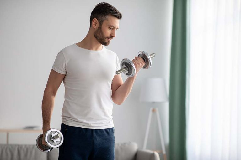 young man strength training with dumbbell