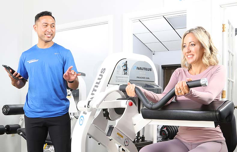 male personal trainer with female client, working out in studio on a machine