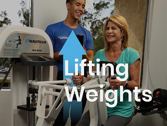 woman over 60 lifting weights with a personal trainer