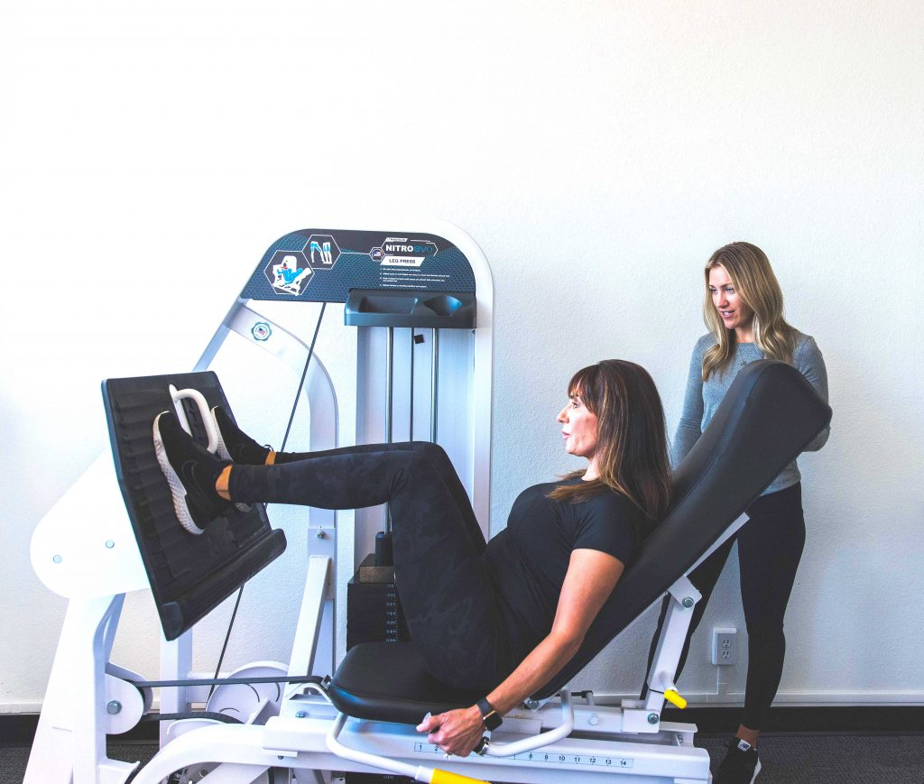 Female Client doing a leg press with a certified personal trainer