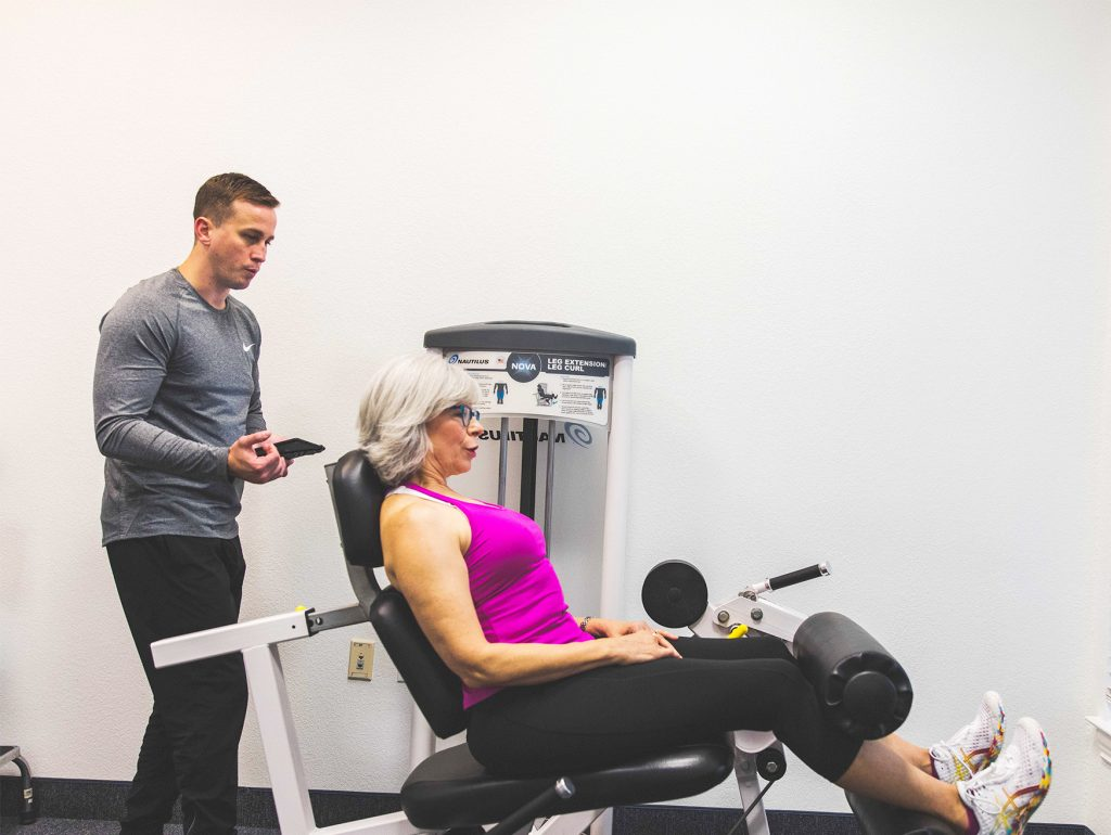 Female client doing a leg curl on an exercise machine with a personal trainer