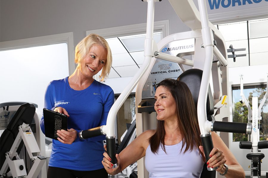 Trainer smiling at client showing client results on chest press