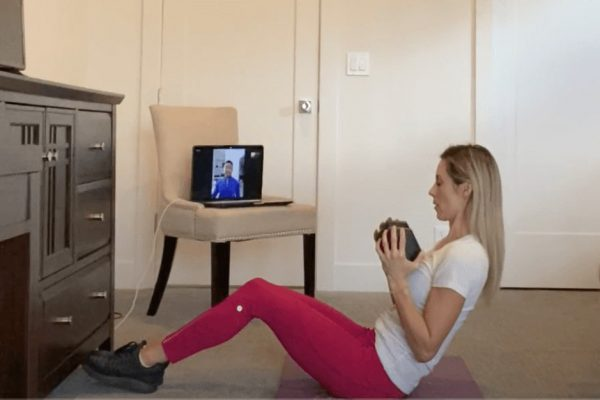 Woman exercising at home with her virtual personal trainer